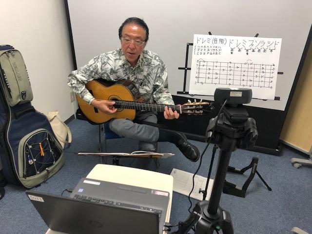 ギターを弾くコーチ